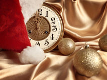 New year. Theme with balls, vintage clock and Santa hat over golden drapery Royalty Free Stock Photography