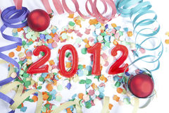 New Year 2012. On the bottom of Christmas balls, confetti and streamers Royalty Free Stock Images