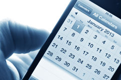 New year 2013. Hand holding smartphone with calendar set on 1 January 2013 stock photography