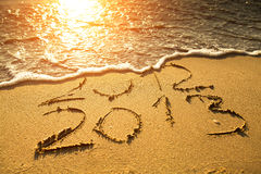 New Year 2013 is coming!. Conceptual photo: New Year 2013 is coming!  - inscription 2012 and 2013 on a beach sand Royalty Free Stock Photography