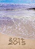 New Year 2015 Is Coming Concept - Inscription 2014 And 2015 On A Beach Sand, The Wave Is Covering 2014 Royalty Free Stock Photos