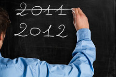 New year. Man writing 2012 on a blackboard Royalty Free Stock Photography