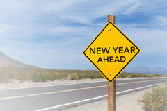 New Year Ahead road sign. With blue cloudy sky and blur background Royalty Free Stock Images