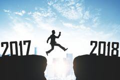 New Year anticipation concept. Man jumping from 2017 to 2018 on sky background. New Year anticipation concept stock photo