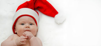 New year baby child. Cute baby child lying on white blanket in red santa hat Stock Images