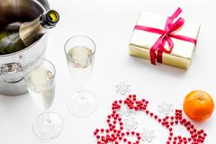 New Year 2018 background. Champagne in bucket, glasses with beverage, tangerines and decoration on white background Stock Photos