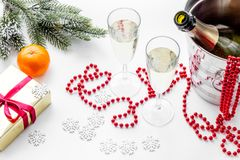 New Year 2018 background. Champagne in bucket, glasses with beverage, tangerines and decoration on white background Royalty Free Stock Photography