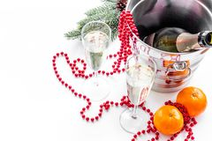 New Year 2018 background. Champagne in bucket, glasses with beverage, tangerines and decoration on white background. New Year 2018 background. Champagne in Stock Photos