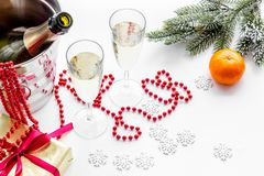 New Year 2018 background. Champagne in bucket, glasses with beverage, tangerines and decoration on white background. New Year 2018 background. Champagne in Royalty Free Stock Photography