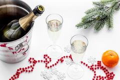 New Year 2018 background. Champagne in bucket, glasses with beverage, tangerines and decoration on white background. New Year 2018 background. Champagne in Royalty Free Stock Photo