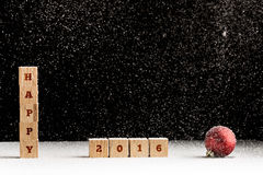 New Year 2016 background with falling snow and a red Christmas b Stock Photos