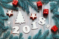 New Year 2018 background -2018 figures, Christmas toys, blue fir tree branches. New Year 2018 still life in cold tones Stock Photos