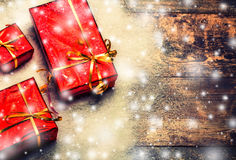 New Year background gift red box with presents on wooden board with snow Stock Photos