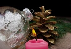 New Year background. New Year`s ball, candle and golden fir cones on a wooden table. New Year`s ball, candle and golden fir cones on a wooden table Stock Photos