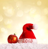 New Year 2015 background and Santa hat. New Year 2015 background.Santa hat ,red christmas ball and snow on golden background Stock Illustration