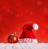 New Year 2015 background and Santa hat. New Year 2015 background.Santa hat ,red christmas ball and snow on red background vector illustration