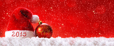 New Year 2015 background and Santa hat. New Year 2015 background.Santa hat ,red christmas ball  and snow on red background Stock Photos