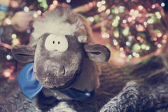 New Year background: sheep and swag. Toy sheep and Christmas lights Royalty Free Stock Image