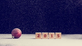 2015 New Year background with snow. Falling onto a red Christmas bauble and row of four wooden blocks with the date numerals - 2015 - over dark background with Royalty Free Stock Photos