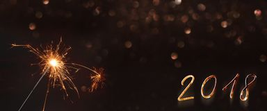 New year background 2018 with a sparkler. Background for the year 2018 with sparkler and golden bokeh Royalty Free Stock Image