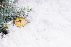 New Year background a vintage clock at midnight. New Year background with green pine branches and a vintage yellow clock on white snow at midnight Royalty Free Stock Image