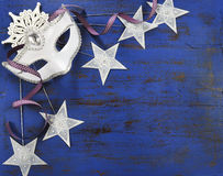 New Year background with white masquerade party mask and stars. Happy New Year background with white masquerade party mask and star decorations on dark blue stock photos