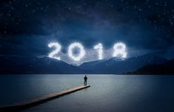 New year background, young man standing on a jetty in a lake and stock photo
