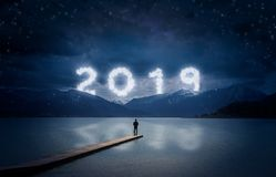 New year background, young man standing on a jetty in a lake and looking to the mountains under the dark sky with cloudy text 2019 royalty free stock photos