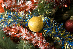 New Year Ball. Yellow New Year's sphere on a celebratory tree royalty free stock photo