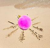 New Year ball in the center of the sun drawn on sand on a beach Royalty Free Stock Photos