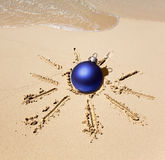 New Year ball in the center of the sun drawn on sand on a beach Stock Images