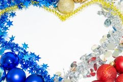 New Year balls and tinsel laid out in the form of a heart. New Year`s red and blue balls and multi-colored tinsel, laid out in the form of a heart Stock Photography