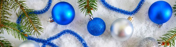 New Year banner with blue and silver Christmas balls in snow, spruce green branches on white background. Xmas decoration. Merry christmas royalty free stock photo
