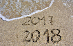 New Year 2018. 2017 and new year 2018 on a beach sand with wave Stock Image