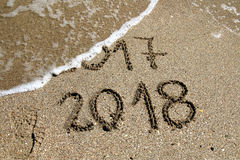 New Year 2018. 2017 and new year 2018 on a beach sand with wave Stock Photography
