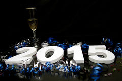 New year 2015 on black with confetti and champagne. New year and graduation 2015 on black floor with blue and black ribbon and confetti Stock Image