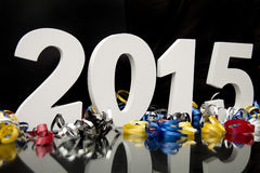 New year 2015 on black with confetti. New year and graduation 2015 on black floor with blue and black ribbon and confetti Royalty Free Stock Image