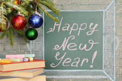New Year!. Books and Christmas decorations before chalkboard with title: Happy New Year Stock Image