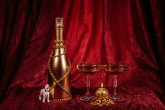 New year Bottle of champagne and candle, glasses and dog on red background royalty free stock photos