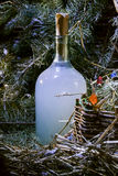 New Year bottle of homemade strong drink vodka moonshine hooch n. Holiday bottle of homemade strong drink vodka moonshine hooch near Christmas tree. Still life royalty free stock photos