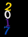 New Year 2017. Bright children's wooden numbers, balanced, on black reflection. Fun. Royalty Free Stock Image