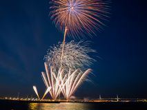 Bright fireworks burst in the blue sky with distant city lights and sea water Royalty Free Stock Photos