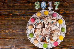 New year cake with lots of candles and macarons near candles num Royalty Free Stock Photography