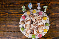 New year cake and macarons as a clock near candles number 2017 o Stock Images