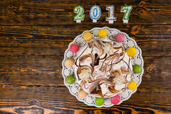 New year cake and macarons near candles number 2017 on wooden ba Stock Photo