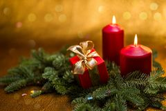 New Year card. Christmas greetings. Red candles with a new year decoration, Christmas tree branches, a gift and a golden backgroun royalty free stock photos