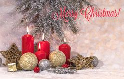 New Year card. Christmas red candles in light Christmas decoration, a wreath of fir branches, glass balls and stars on a light bac royalty free stock photo