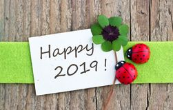 Happy, Lucky New Year 2019. New Year card with leafed clover and ladybugs on wooden background Stock Photos