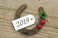 New Year card for 2019. New Year`s Card with horseshoe, Leafed clover and ladybugs on wooden background Stock Photo