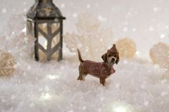 New Year card with toy dog in a fairy forest on winter background with snow and lights. royalty free stock photography